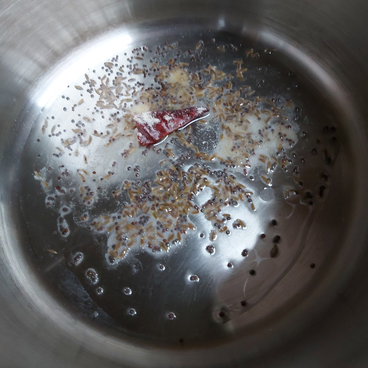 In a pan or vessel, heat the oil and splutter 1/2 teaspoon of mustard seeds and 1/2 tablespoon cumin seeds. Add 1-2 broken red chili and asafoetida. Fry.
