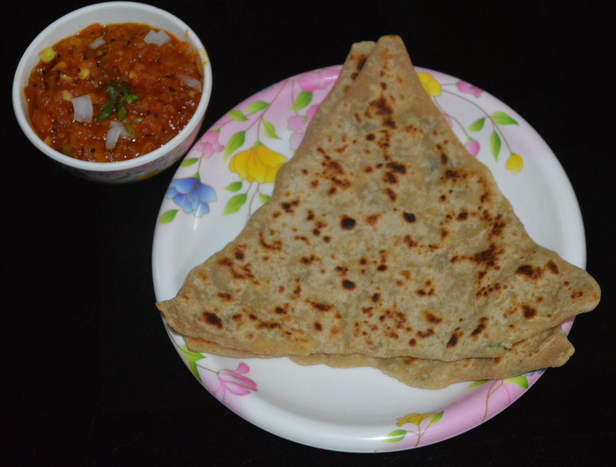 Paneer paratha served with tomato salsa.