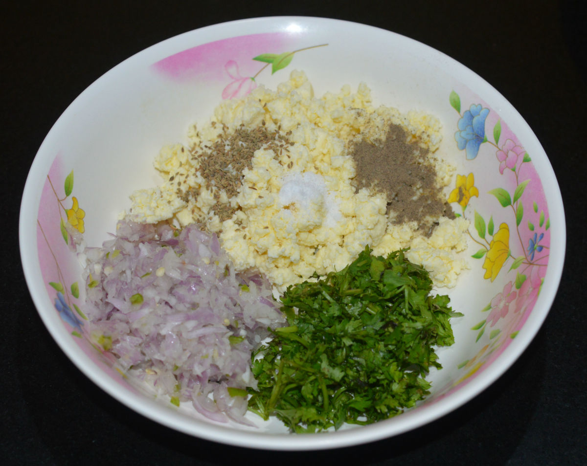Step two: In a mixing bowl, add crumbled paneer, chopped onions, coriander leaves, carom seeds, pepper powder, and salt. Mix well. This is the stuffing for the parathas.