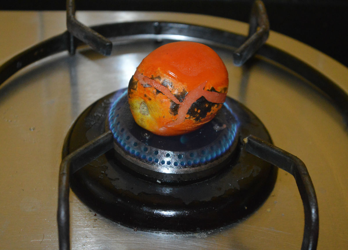 Step one: Roast the tomatoes on a gas stove.
