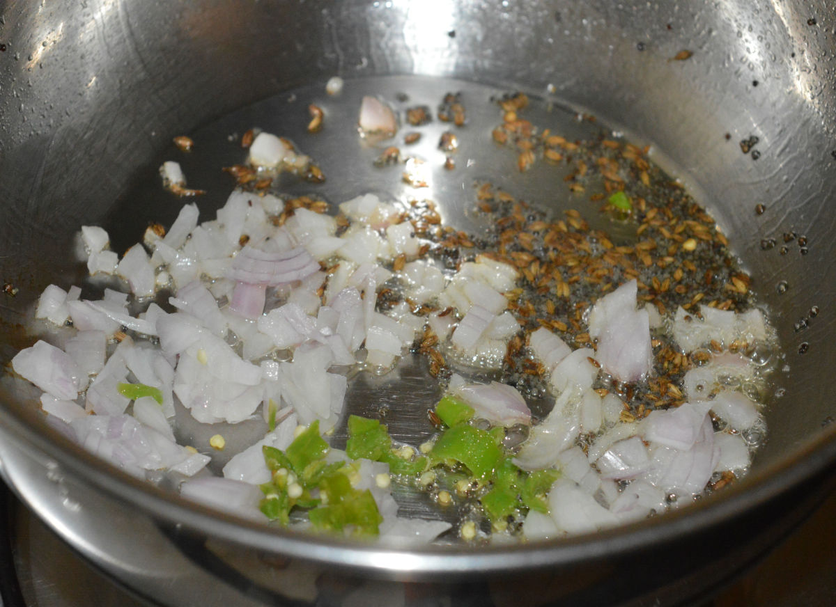 Step two: Heat oil in a deep-bottomed pan. Throw in mustard seeds and cumin seeds. Let them crackle. Add chopped onions and green chilies.