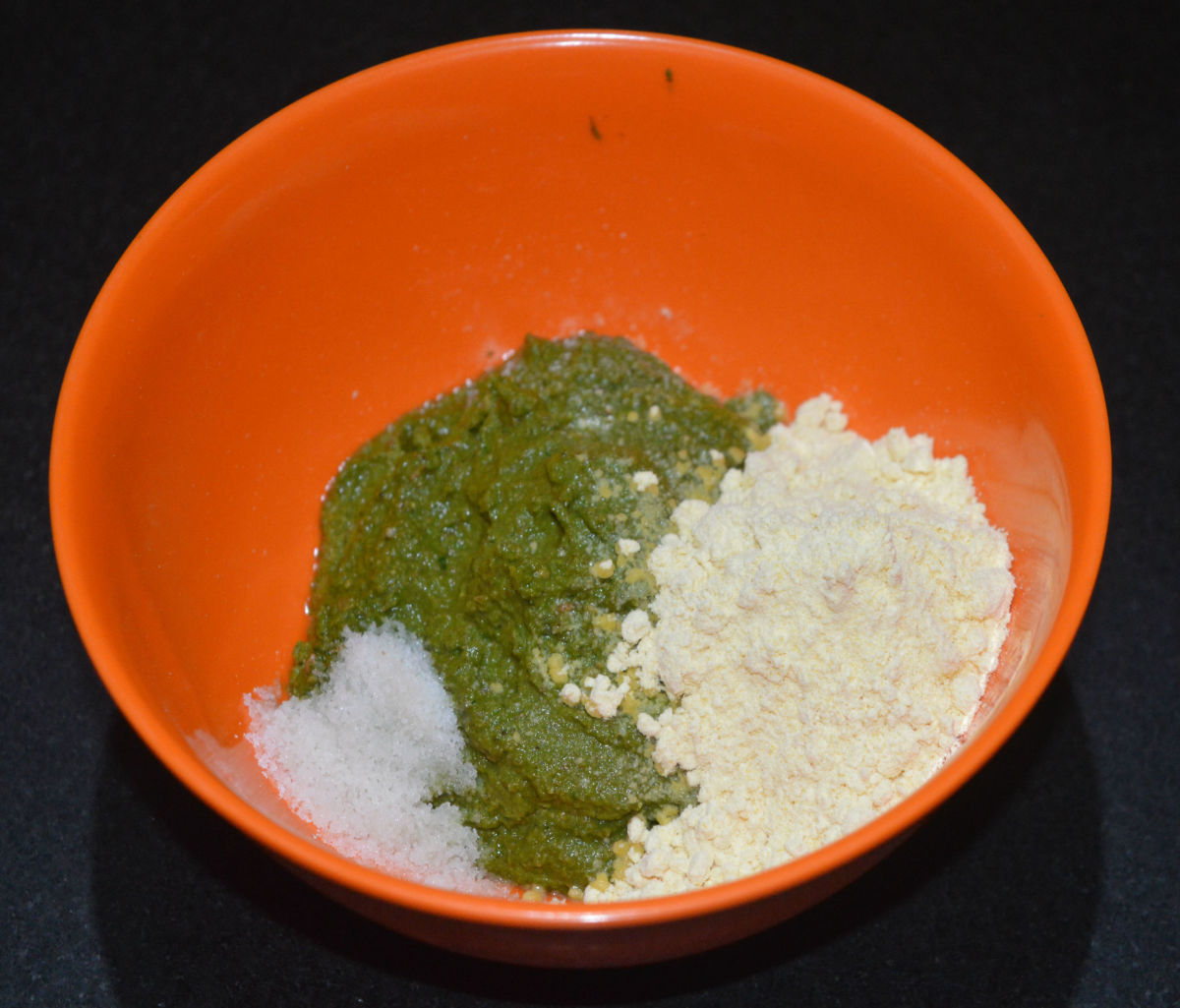 Step three: Transfer the paste to a mixing bowl. Add chickpea flour (besan) and salt. Add 2 tablespoons of water and mix well.