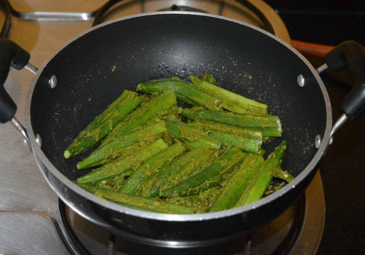 Step six: Place the stuffed okra on it one near the other. Cook it on medium heat for 2-3 minutes. Sprinkle a few drops of water if needed. Turn the okra.
