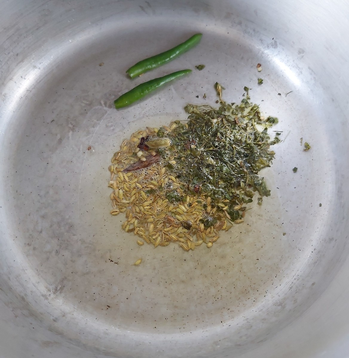 Add 1 teaspoon of fennel seeds, 1-2 teaspoons of kasuri methi or dry fenugreek leaves and 1-2 slit green chilies. Fry for a minute.