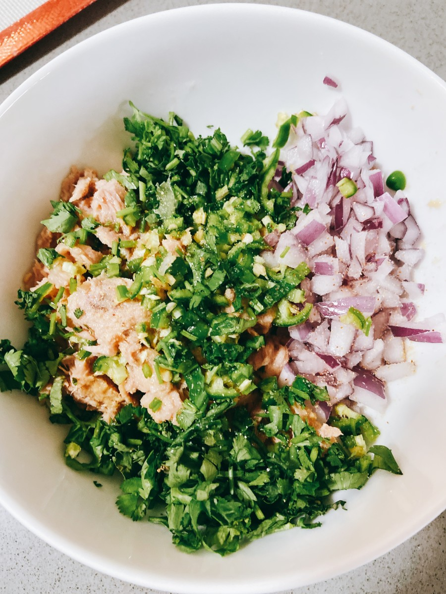 In a bowl, combine the tuna, chopped onion, serrano pepper, red onion, salt, pepper, lime juice, and mayonnaise.