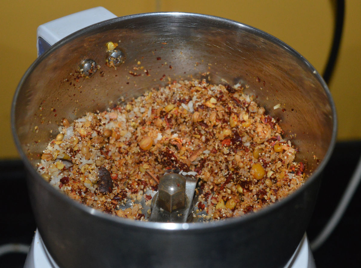 Roasted ingredients added to a mixer jar for making vangibath powder.