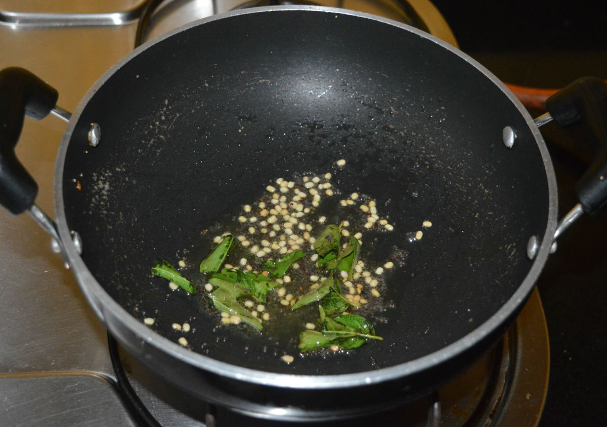 Step two: In the same pan, add some oil or oil and ghee mixture. Keep the heat at medium. Throw in mustard seeds and let them crackle. Add white lentils and curry leaves. Saute until the white lentils become golden brown.