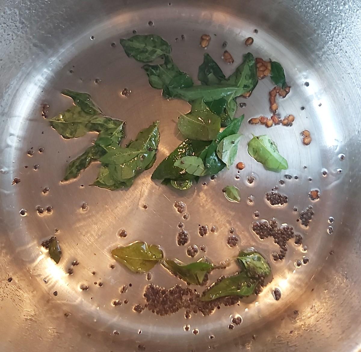 In a pan or pot, heat 1-2 teaspoons of oil, splutter 1/2 teaspoon of mustard seeds, 1/4 teaspoon of fenugreek seeds or methi seeds and 1-2 strings of fresh curry leaves. Fry till curry leaves turn crisp.