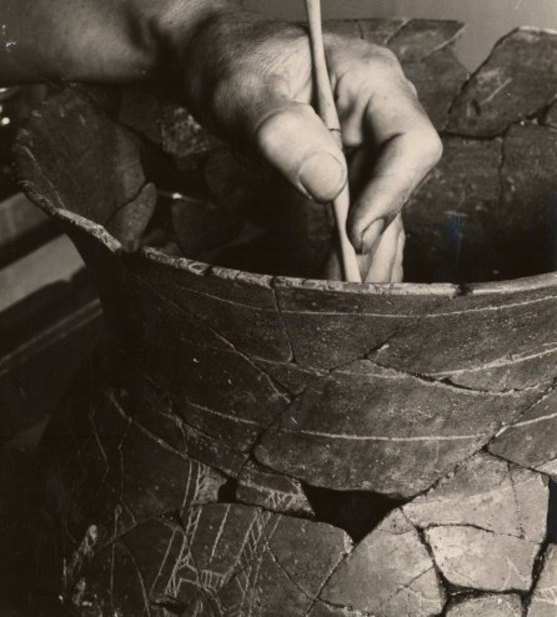 Restoring pottery found at Spiro Mounds
