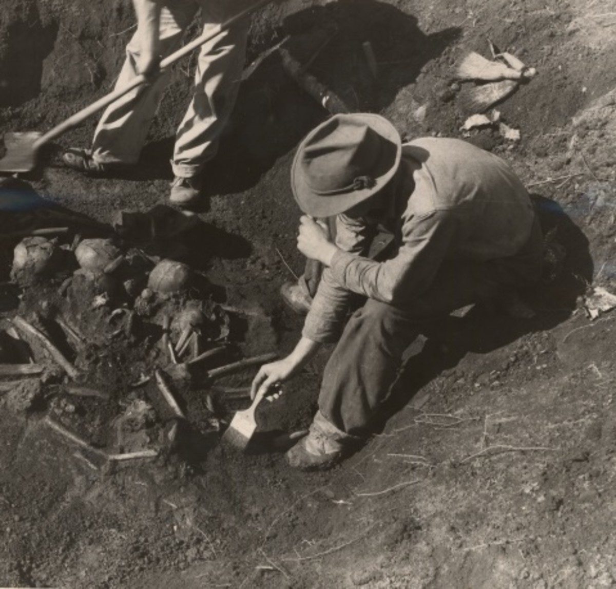 WPA Laborers excavate the burials by trained archaeologists by using brushes and steel needles.