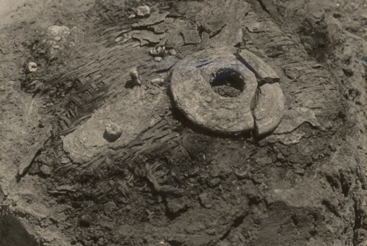 Ear-spool and human teeth found on a fragment of matting