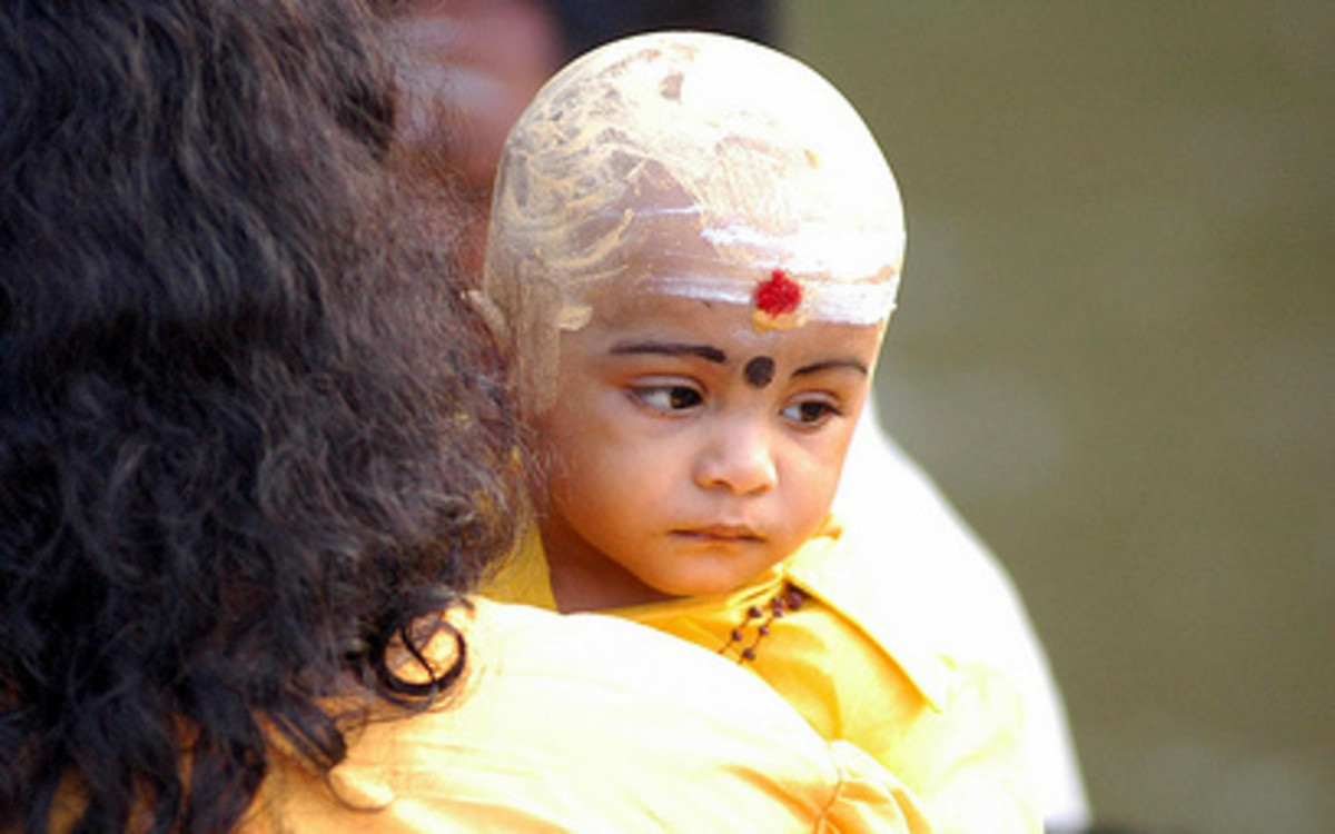 A child with shaved head, as part of penance for the minor during Thaipusam