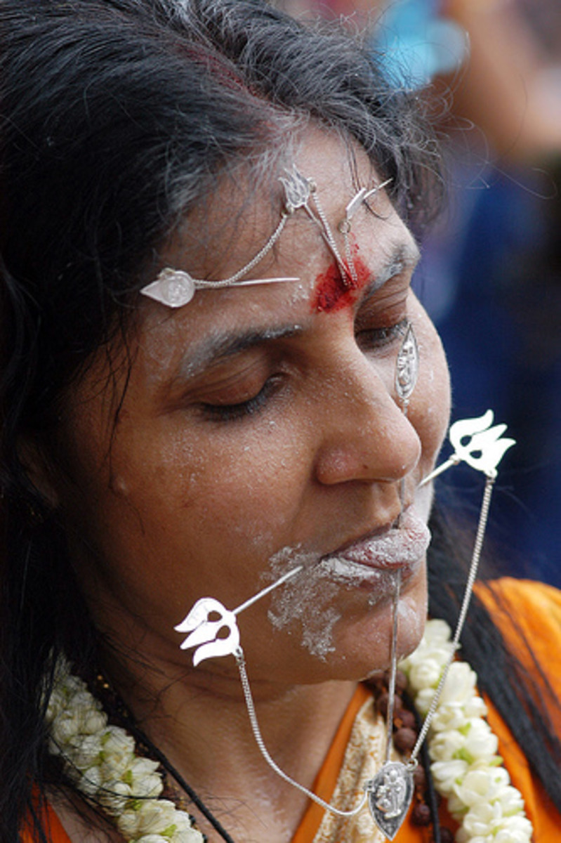 A women devotee who has opted to have her penance done by having a metal skewer pierce through her mouth and part of forehead during Thaipusam celebration