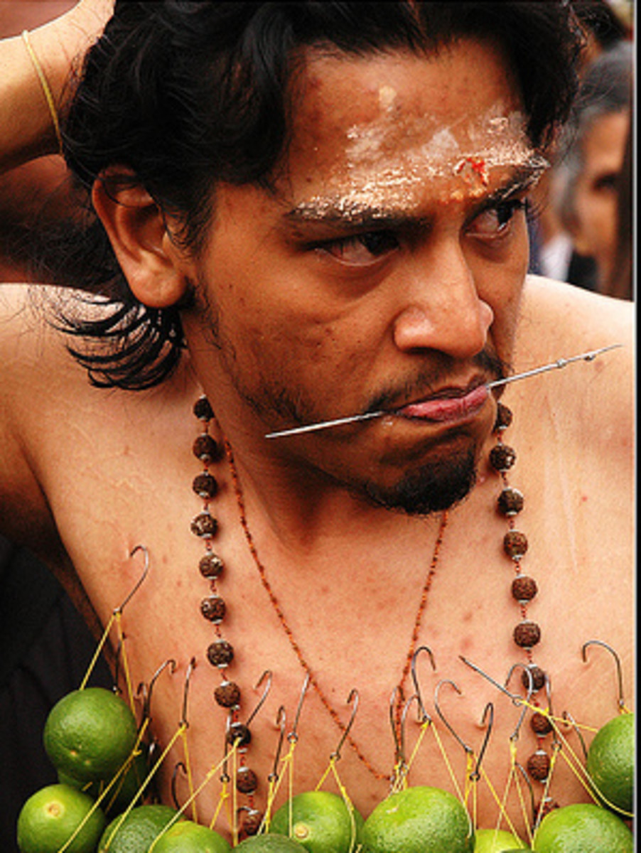 Devotee piercing mouth with small skewer and hanging limes to the body for Thaipusam festival