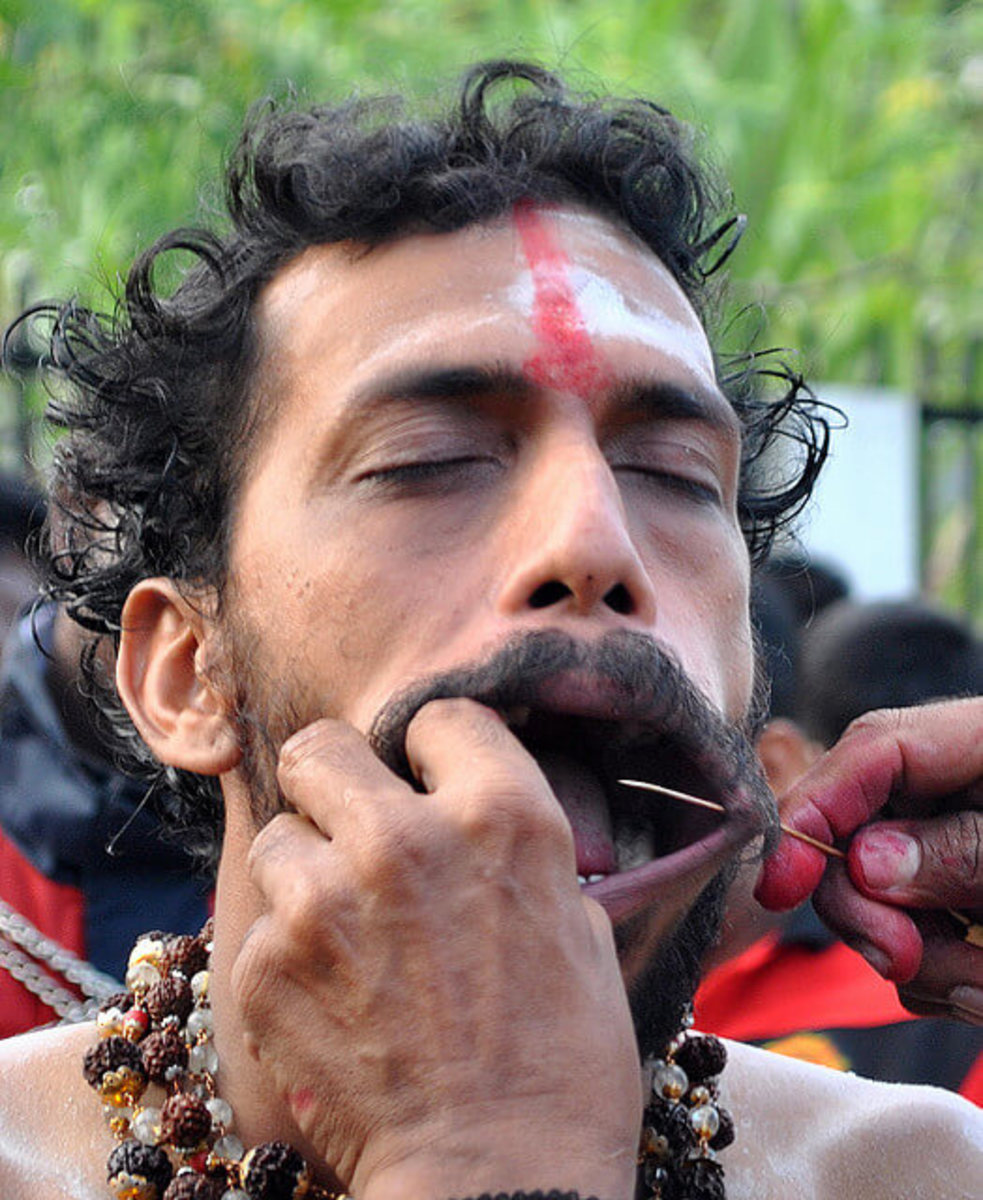 Worshipper being pierced to allow for spikes that will be placed through his cheeks.