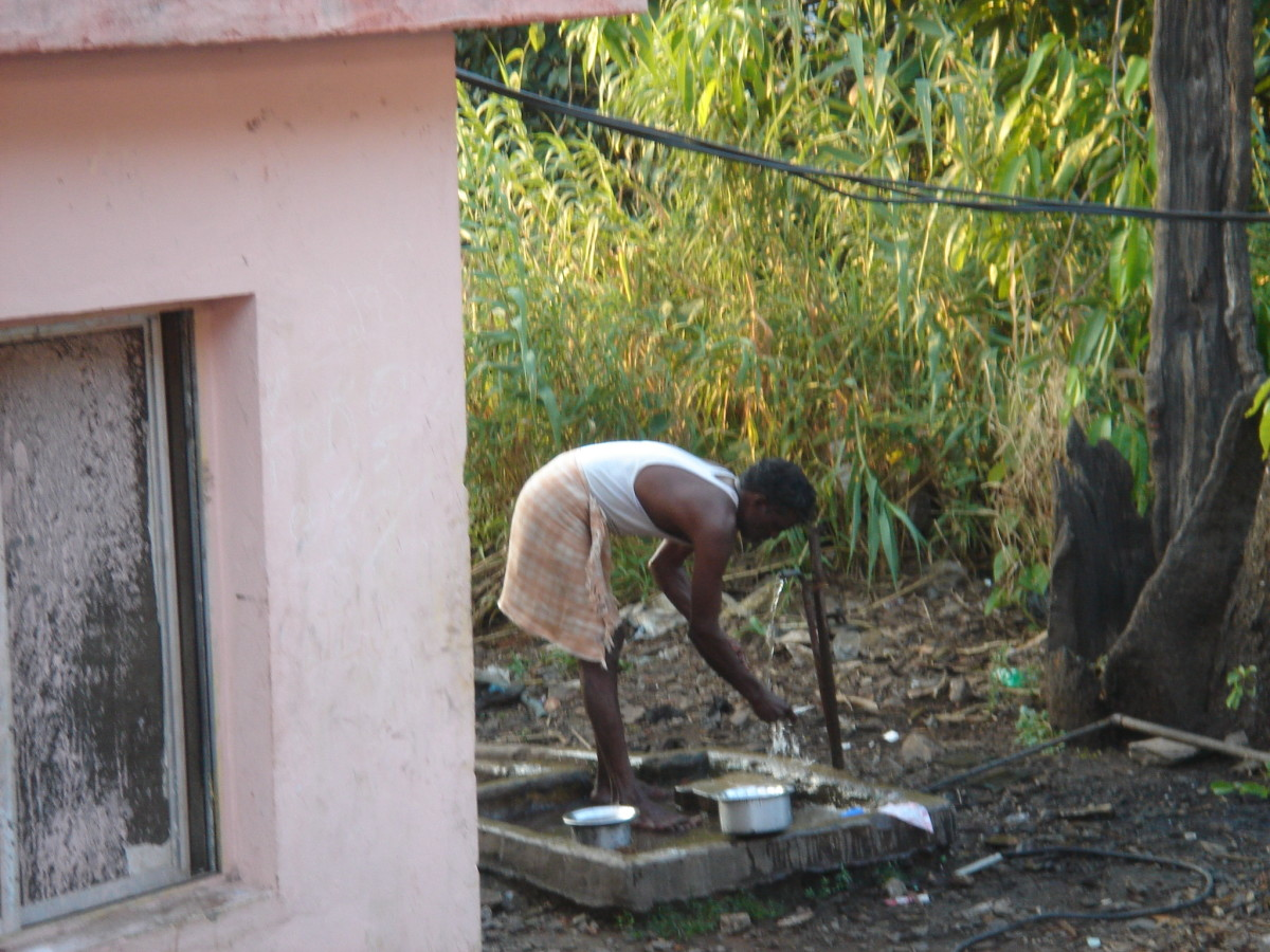 This man is standing and leaning over a spigot to wash dishes in India.
