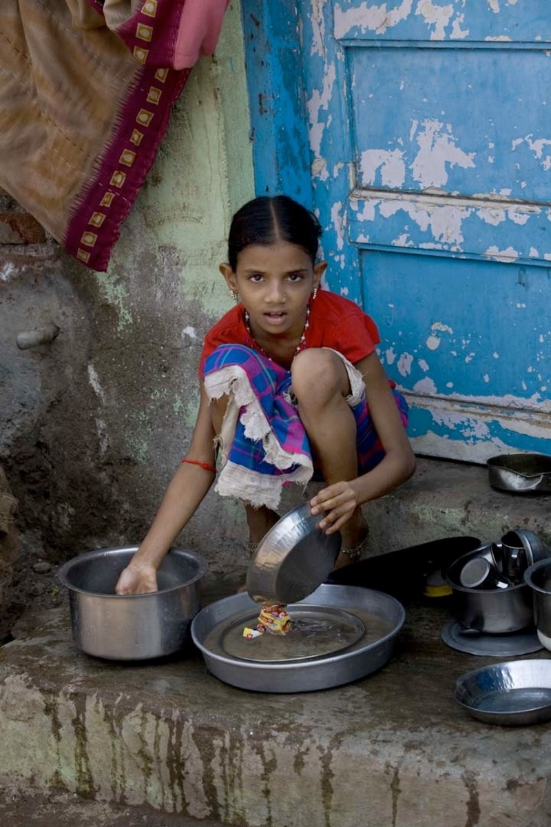 This girl is washing dishes in Mumbai, India.