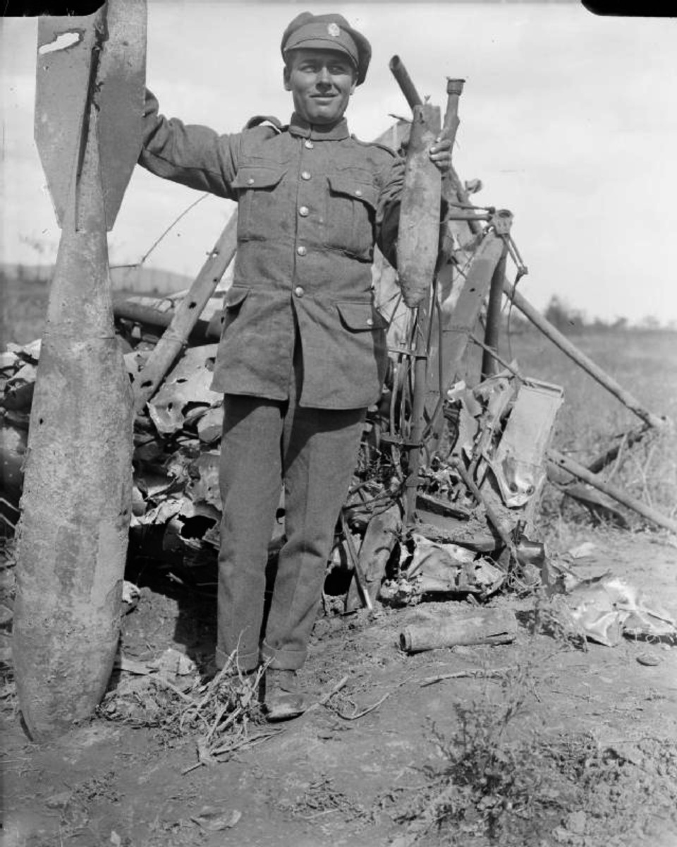 WW1: British serviceman with a large and smaller bomb from the wreckage of a twin-engined Gotha bomber aircraft at Ravelsberg Camp.