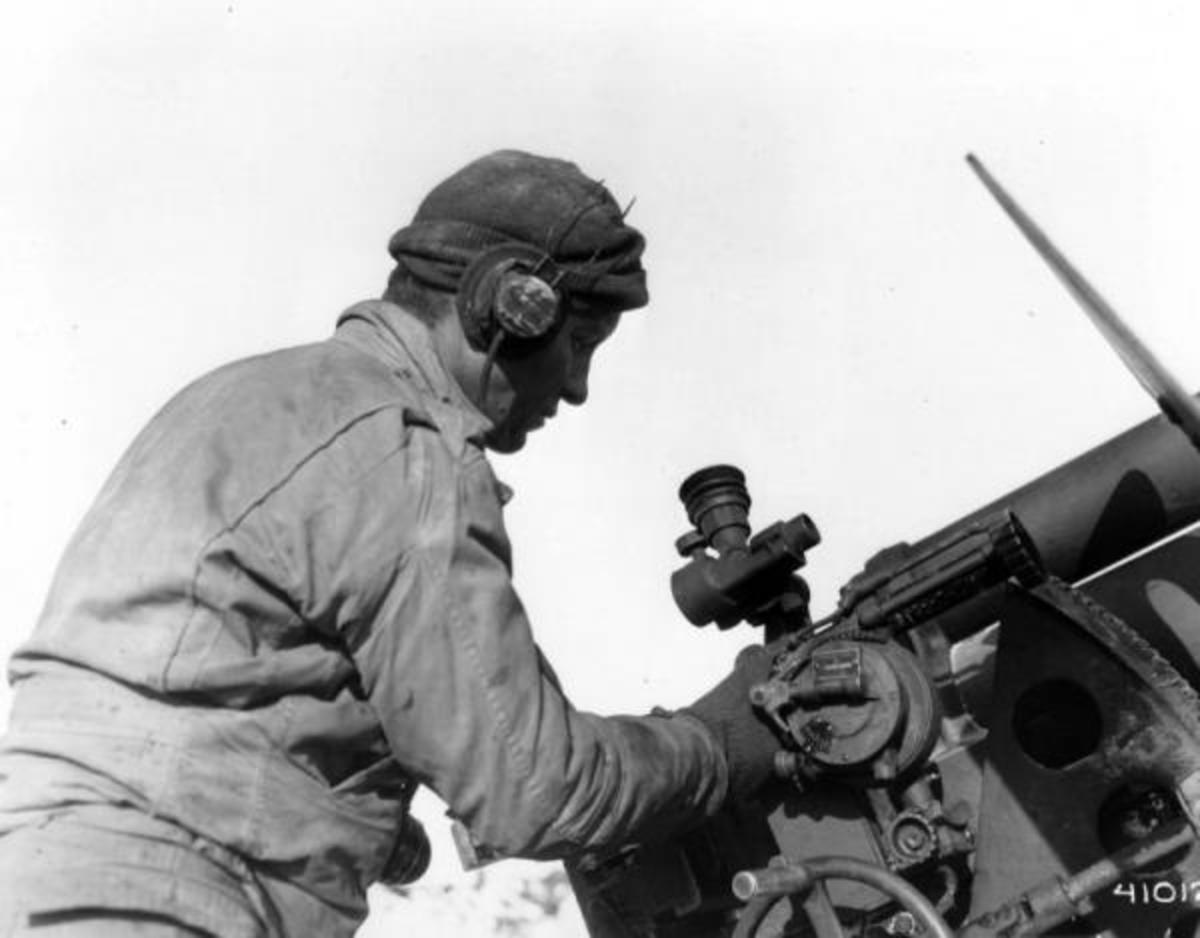 The #1 gunner on a 105mm howitzer (right side of the breech), checking his scope. He controlled the elevation of the tube.