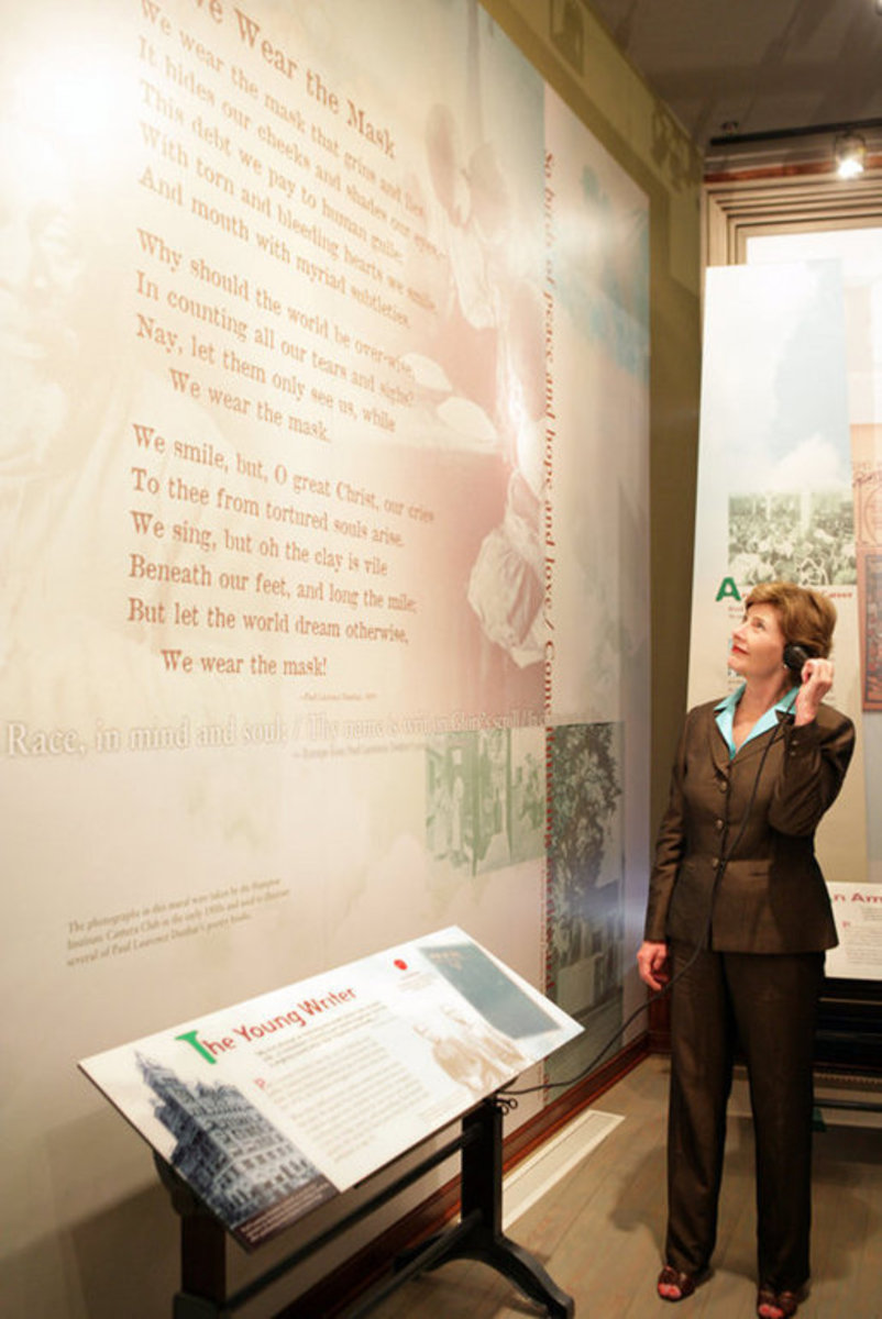 Mrs. Laura Bush listens to a reading of a Paul Laurence Dunbar poem during a tour of the Wright-Dunbar Village, a Preserve America neighborhood honoring the Wright brothers and Dunbar, in Dayton, Ohio. Photo taken Wednesday, August 16, 2006.