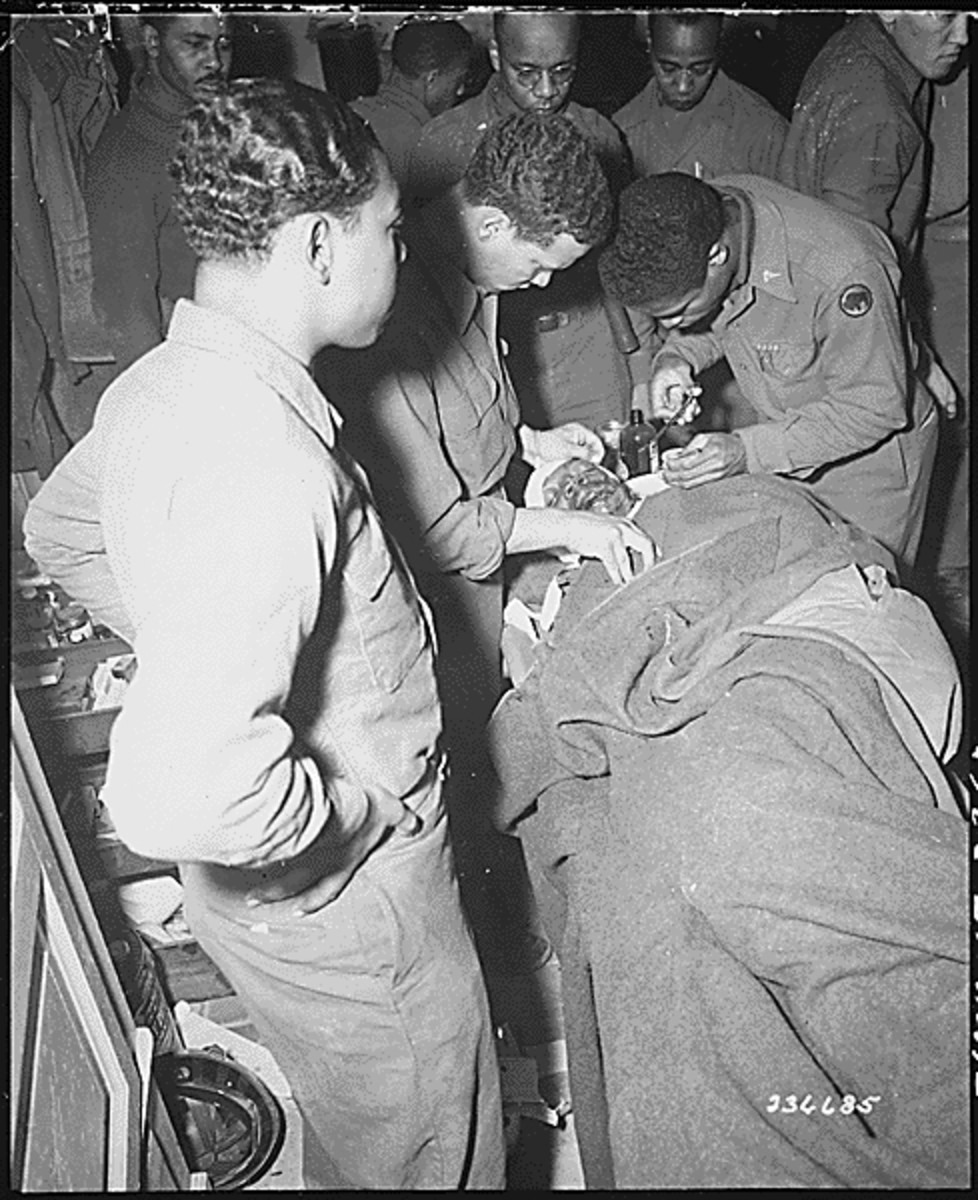 Bullets don't discriminate: 92nd ID soldier receiving treatment for a facial wound, Feb. 1945