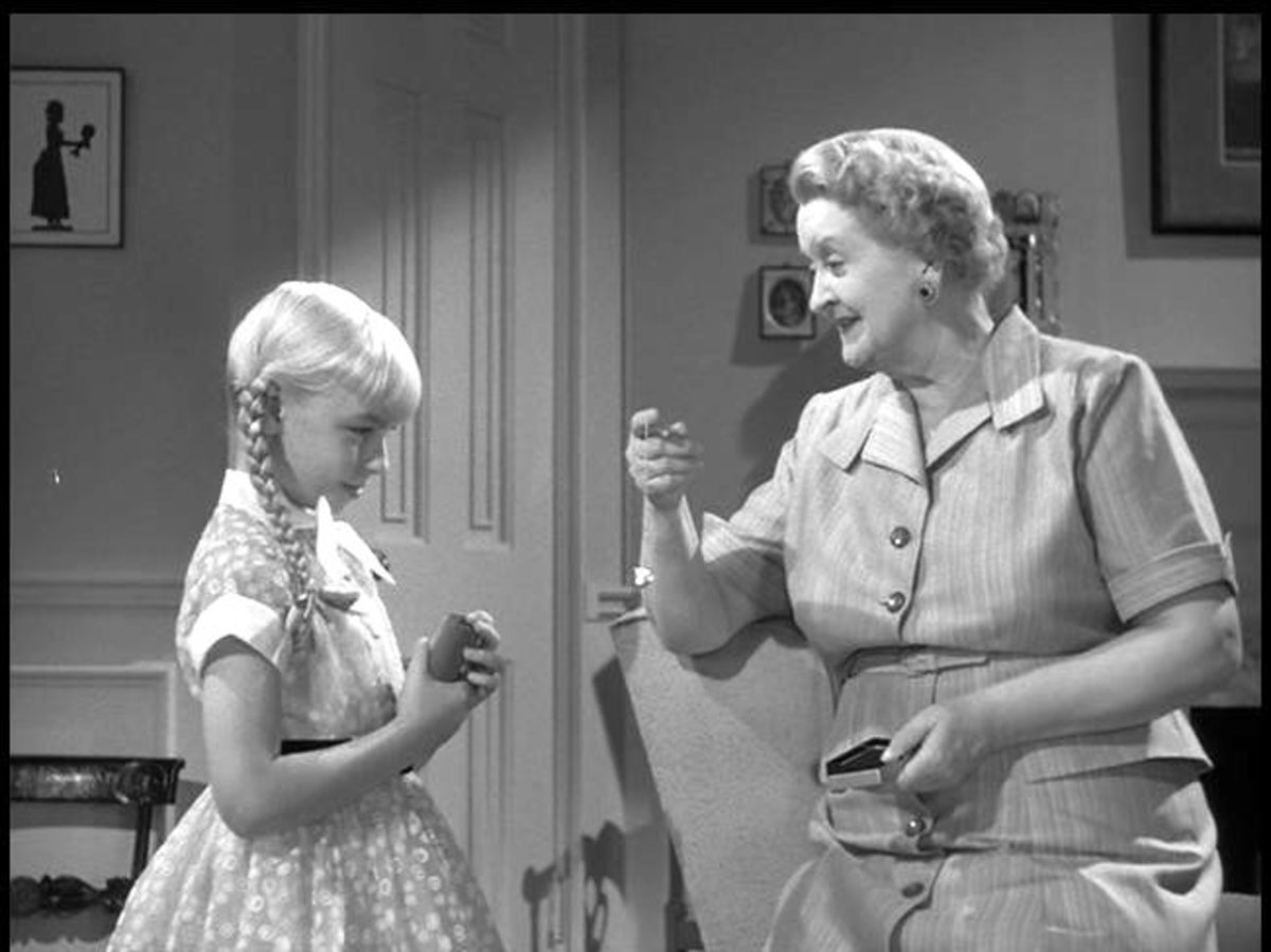 Mrs. Breedlove (Evelyn Varden) offers a gift to Rhoda. This helps display Rhoda's preoccupation with material items.