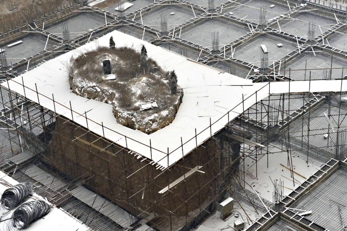 Scaffolding, a platform and a bridge, allowing the graves to be exhumed from the snow-capped mound