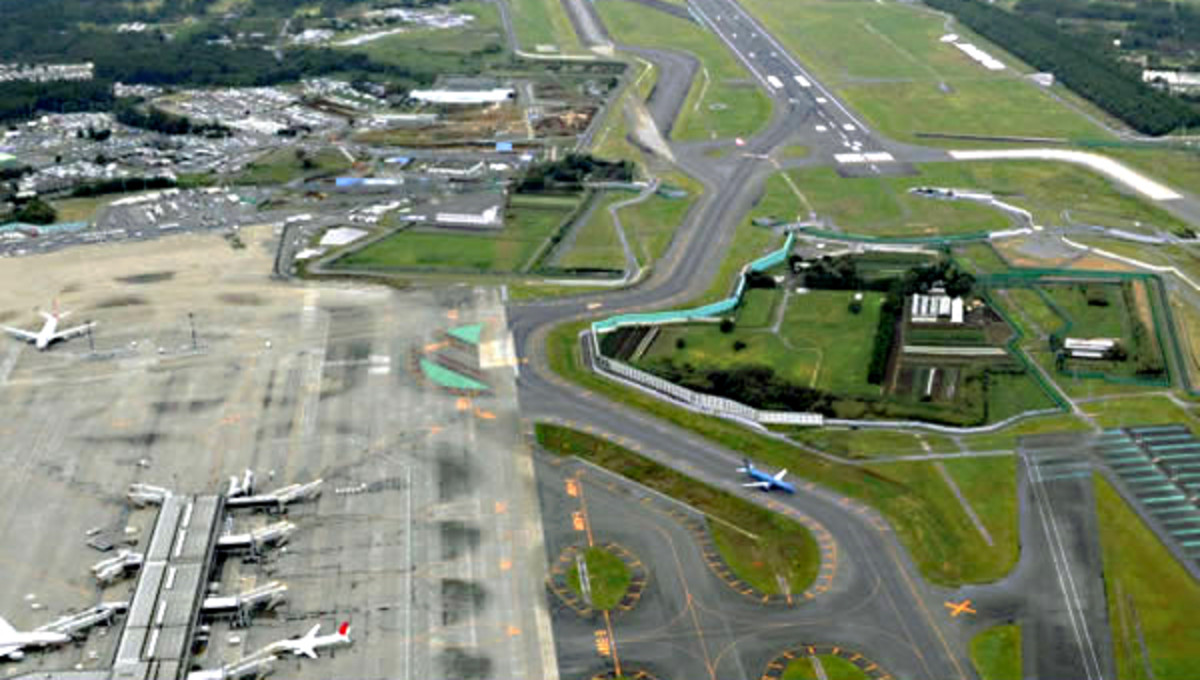 Narita Airport. Note the aeroplanes parked at the terminal on the lower left, the runway at the top, and of course the farmland in the middle of the airport