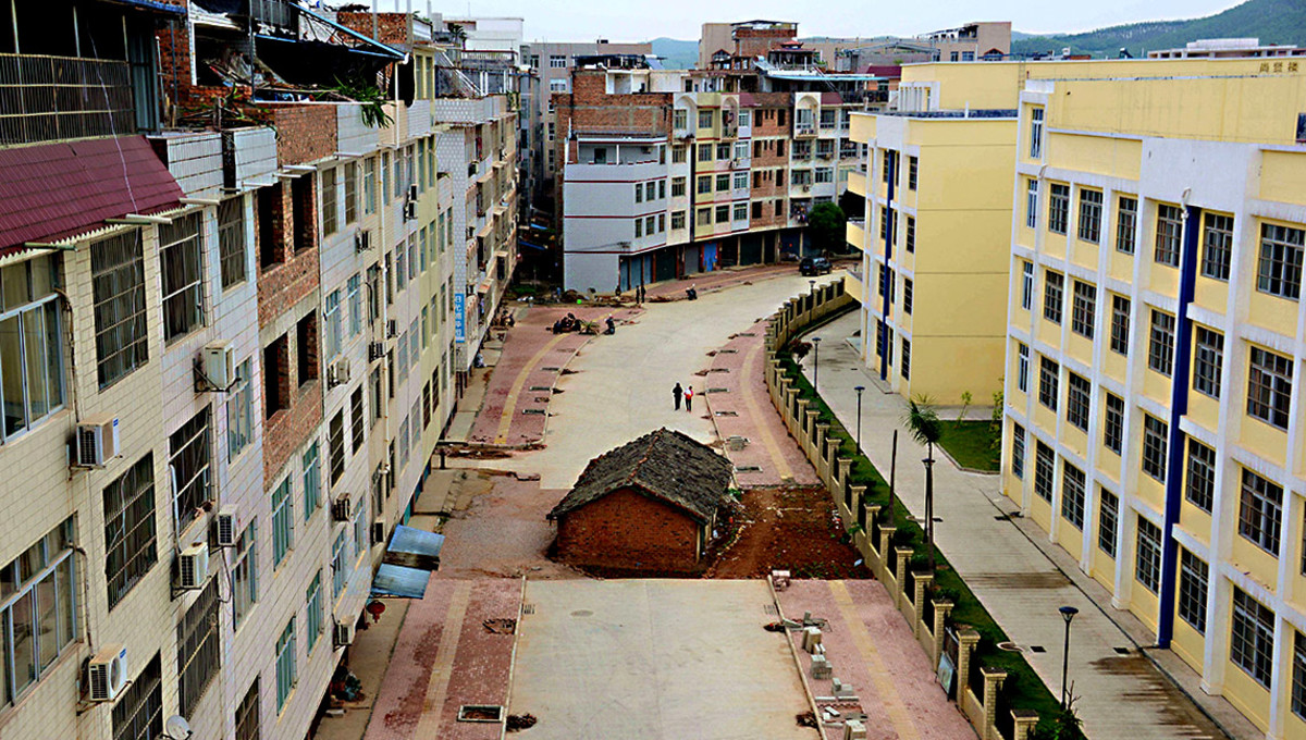 A new road and new buildings on either side and a development almost complete - but for the obstacle in the middle - the tiny nail house of Nanning