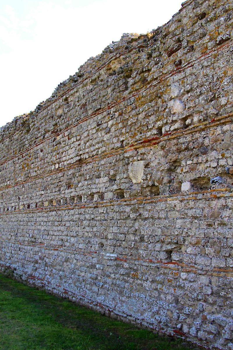 The characteristically imposing Roman wall on the north side of Rutupiae, built of flint stone, concrete and tiles, c 273 AD and still largely intact today