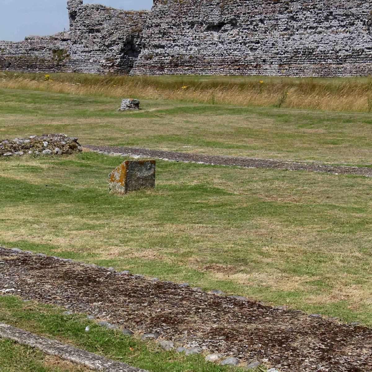 All that remains of the 12th century chapel at Richborough are these foundations and some concrete markers in the foreground. The north wall of the Roman fort stands in the background beyond a trench