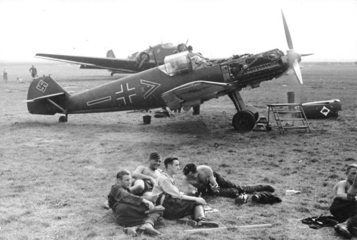 German pilots waiting for a mission their Messerschmitt BF109s in the background.