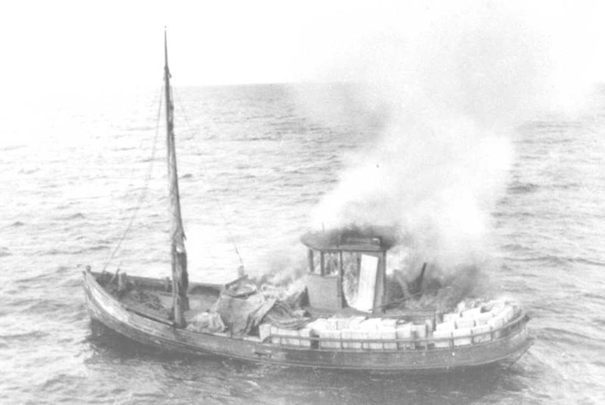 The crew of this boat has set their vessel on fire to destroy the evidence they are smuggling contraband liquor.