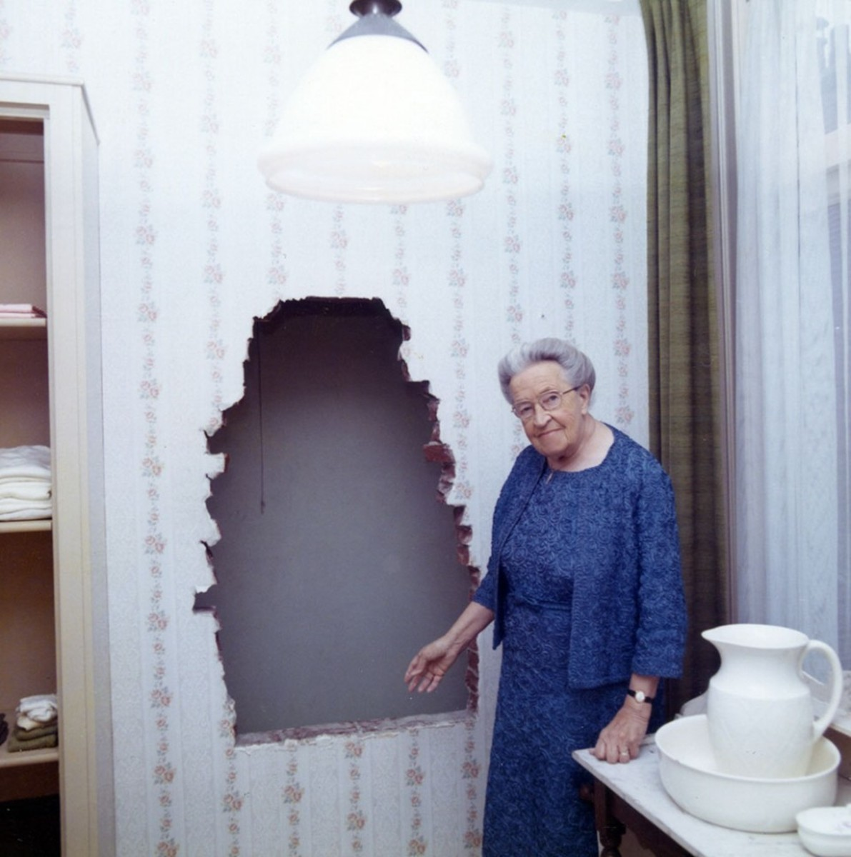Corrie ten Boom Shown Pointing Out the Entrance to the Hiding Place Behind the Wall in What Had Been Her Bedroom