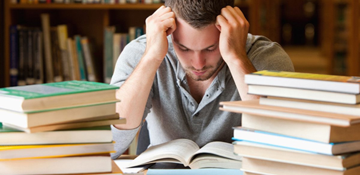 Guy studies on desk surrounded by books