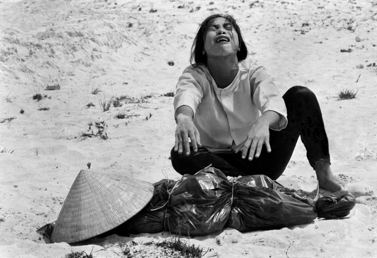 A woman mourns over the body of her husband after identifying him by his teeth, and covering his head with her conical hat. The man's body was found with forty-seven others in a mass grave near Hue, April 11, 1969.