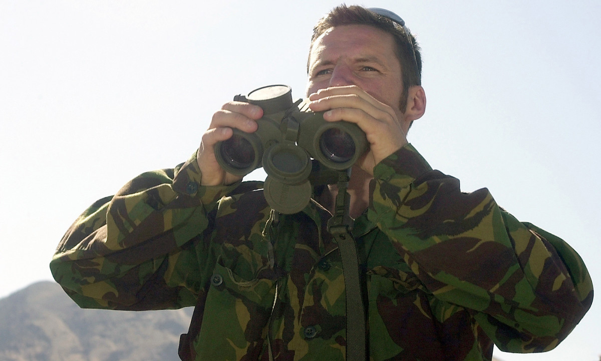 A British SAS agent locates a target using binoculars.
