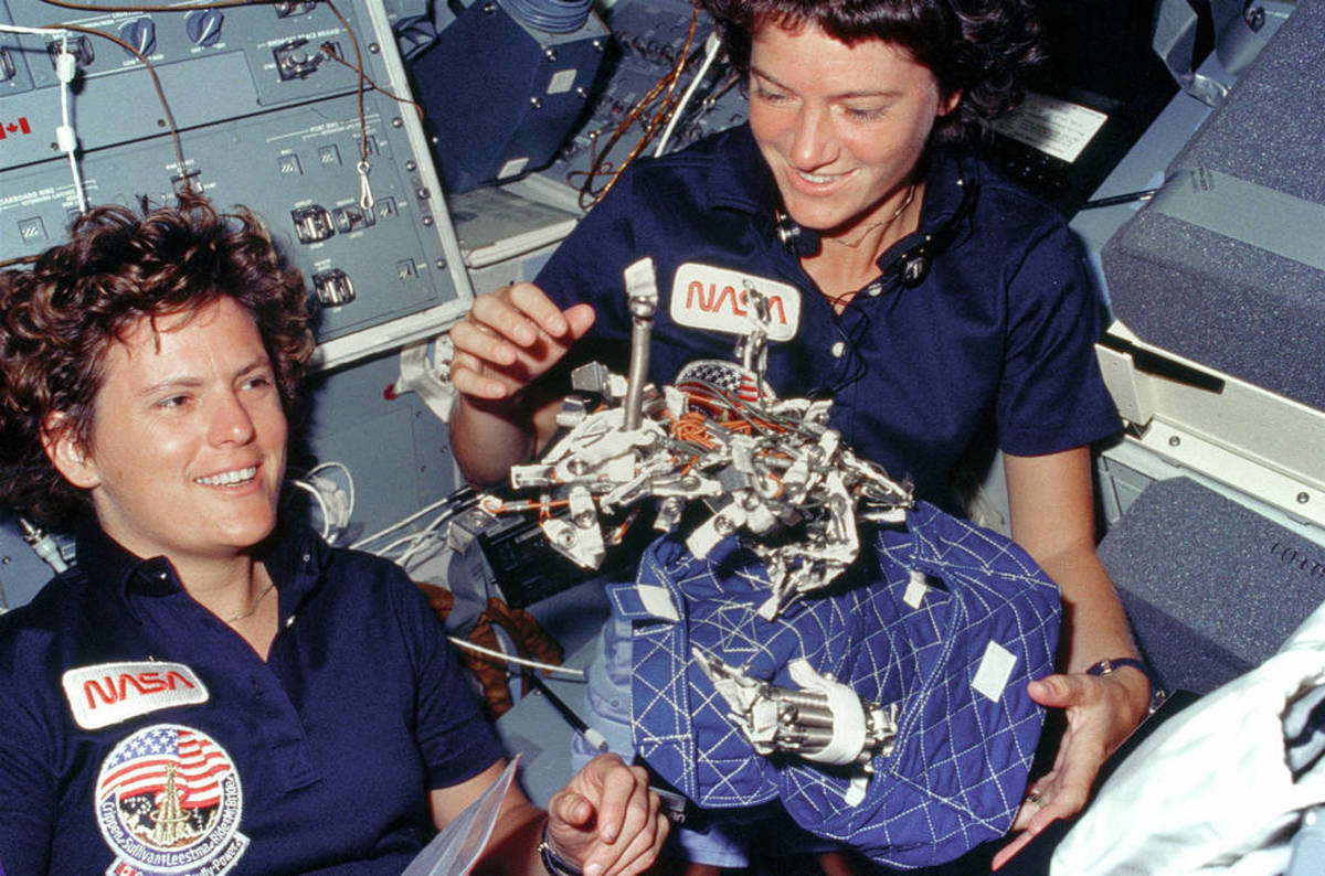 Kathryn Sullivan (left) and Sally Ride playing with sleep restraint on board Challenger mission STS-41G