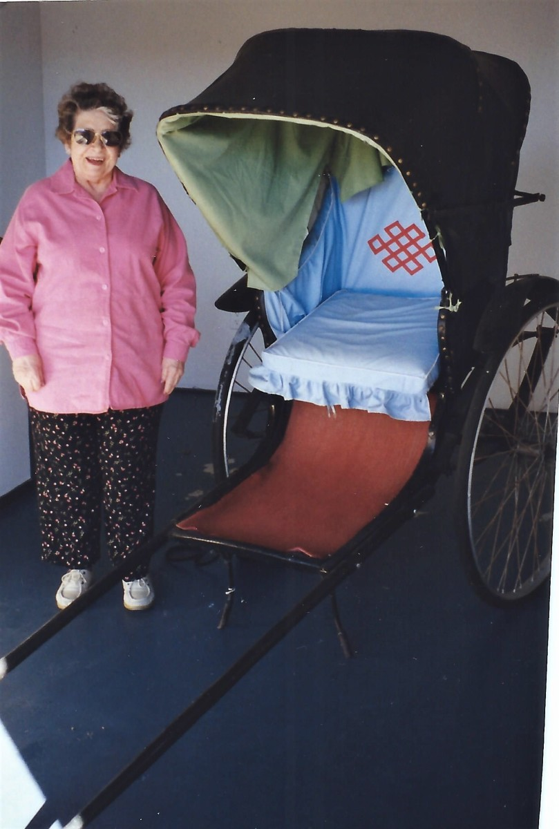 My mother-in-law standing next to a sedan chair