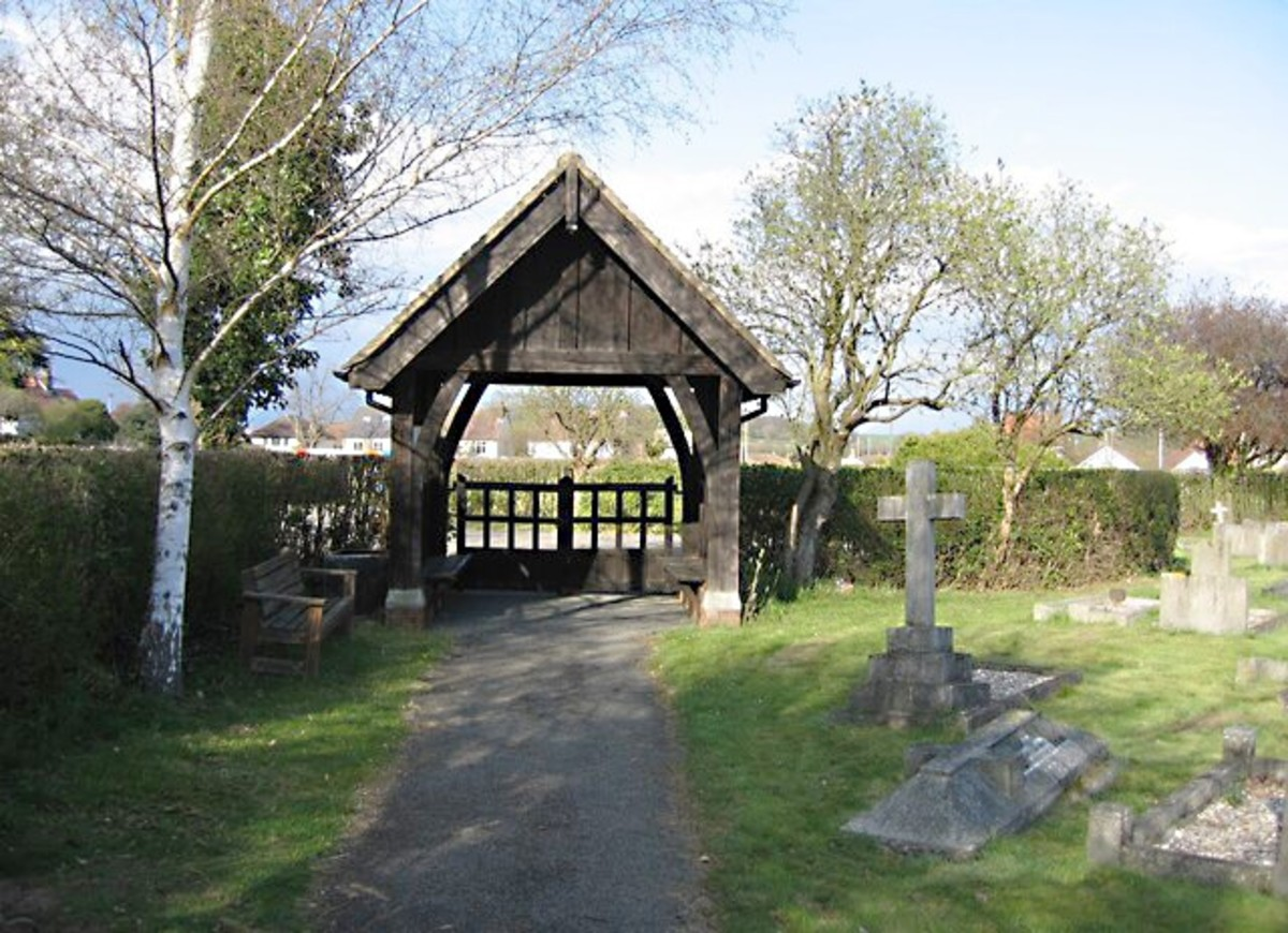 A lych gate is a gateway with a roof found at the entrance to a churchyard.  This lych gate is located in Great Shelford.