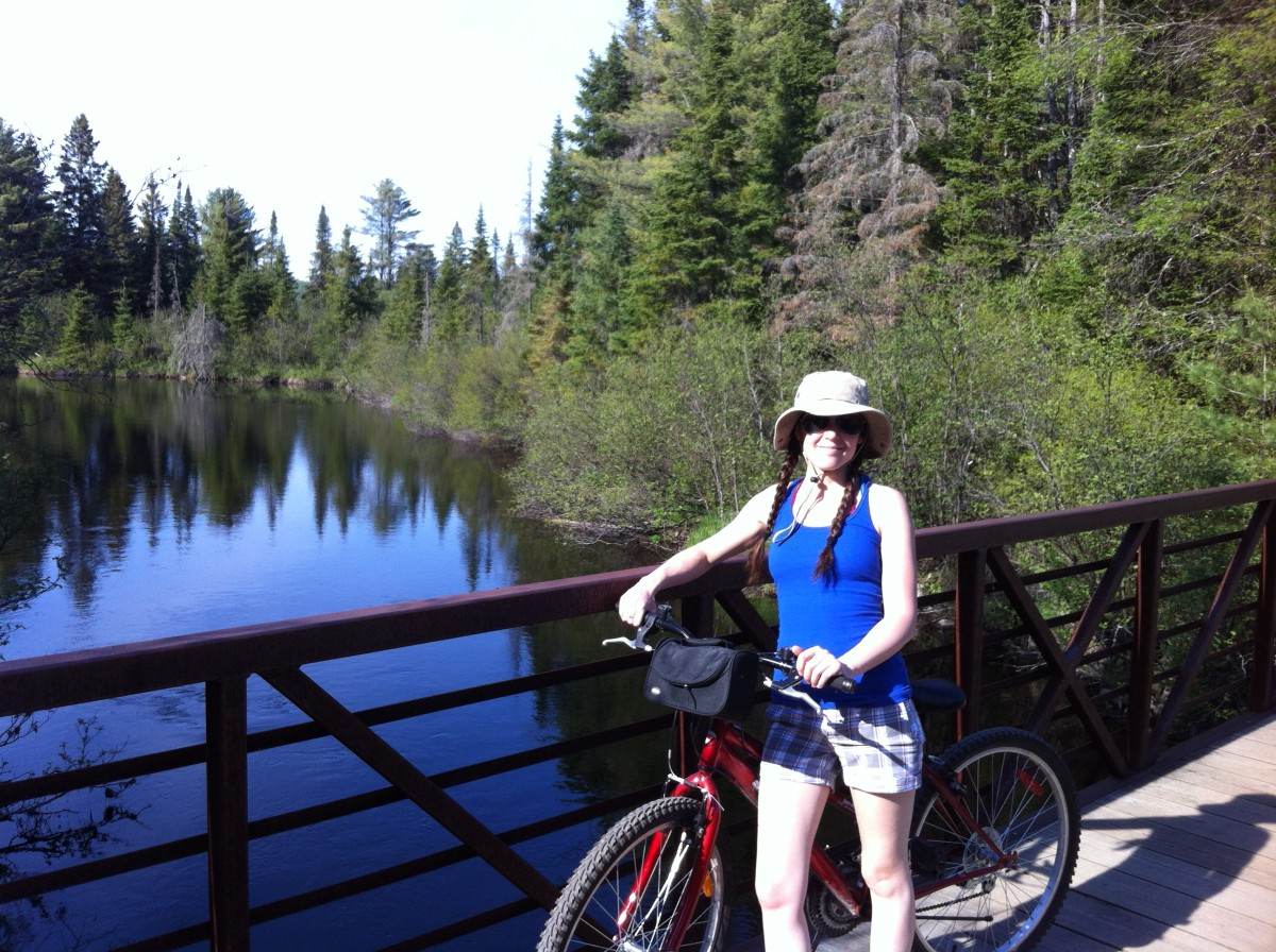 The author, Jessica, taking a break from mountain biking to enjoy the view. Taken along the bike trails of Mew Lake campground, Algonquin Park.