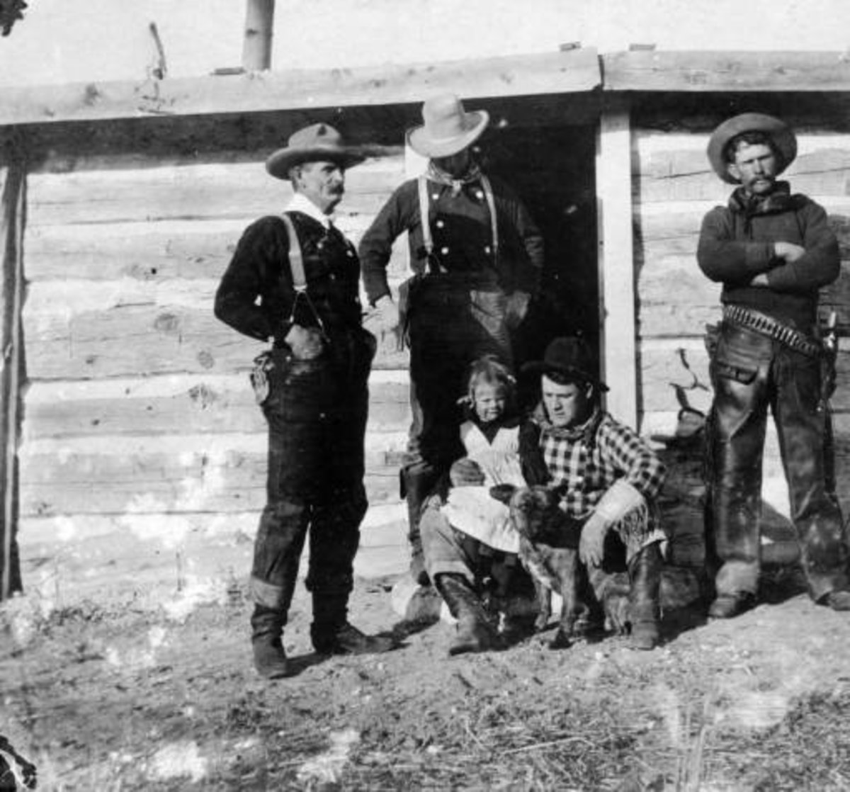 """Real cowboys with a girl and a dog in Converse County, Wyoming; costume includes suspenders, bandanas, leather chaps, a pistol, holster, and ammunition belt. They are identified as: """"Tom Black"""" """"Chas Mayo"""" """"Tex Biddick"""" and """"Neal Hart."""""""