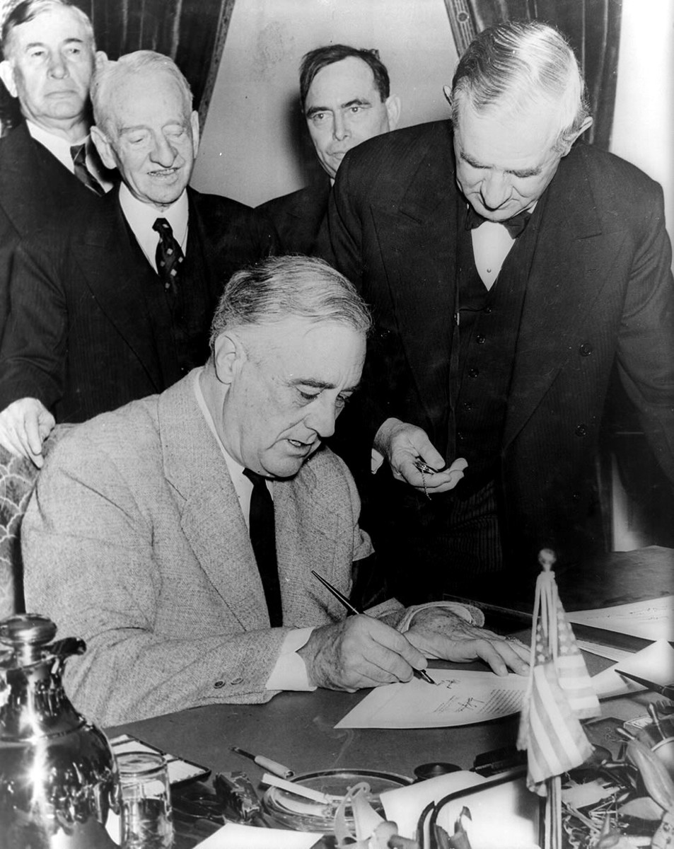 12/11/1941 - United States President Franklin D. Roosevelt signing the declaration of war against Germany, marking US entry into World War II in Europe. Senator Tom Connally stands by holding a watch to fix the exact time of the declaration.