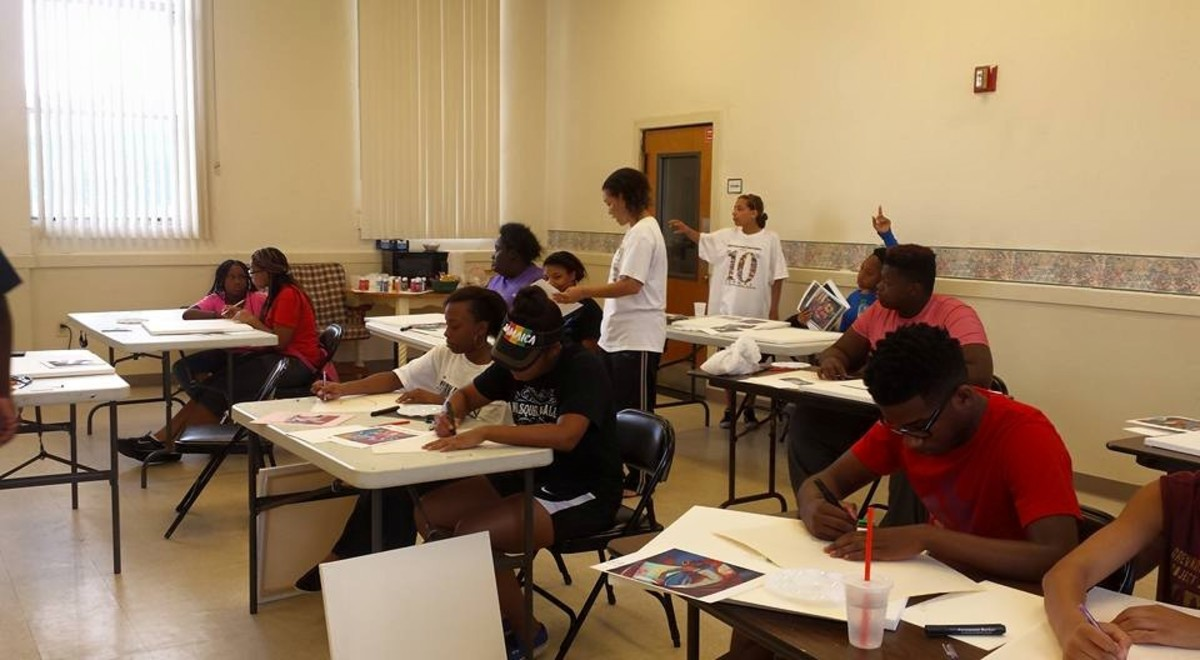 The author conducting a painting workshop with a group of young people.