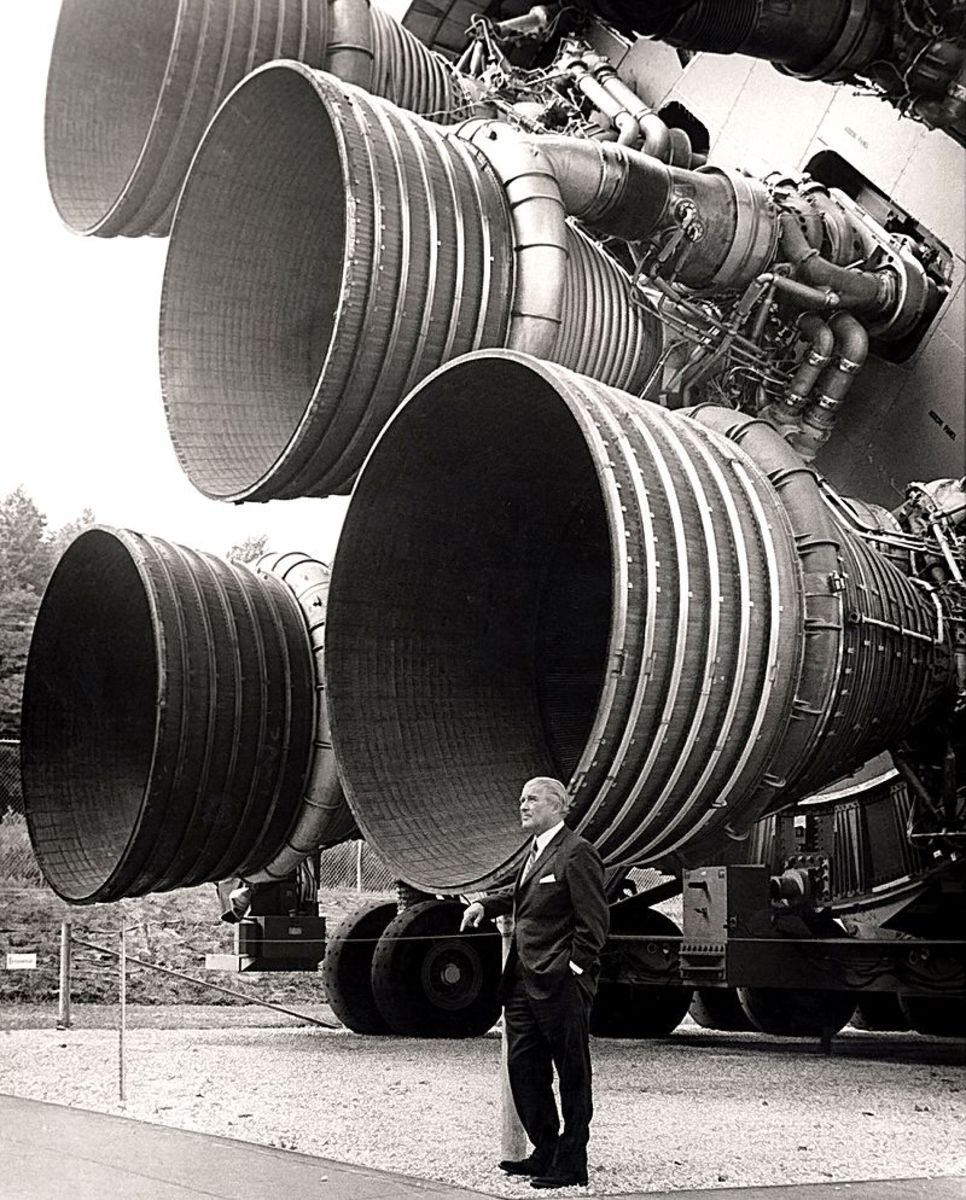 Von Braun in front of the Saturn V rocket engines the most powerful ever built a product of his creation they would land man on the moon.
