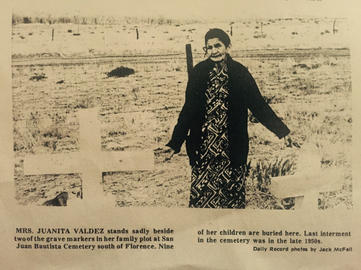 """Mrs. Juanita Valdez stands sadly beside two of the grave markers in her family plot at San Juan Bautista Cemetery south of Florence.  Nine of her children are buried here.  Lat internment in the cemetery was in the late 1950s."""