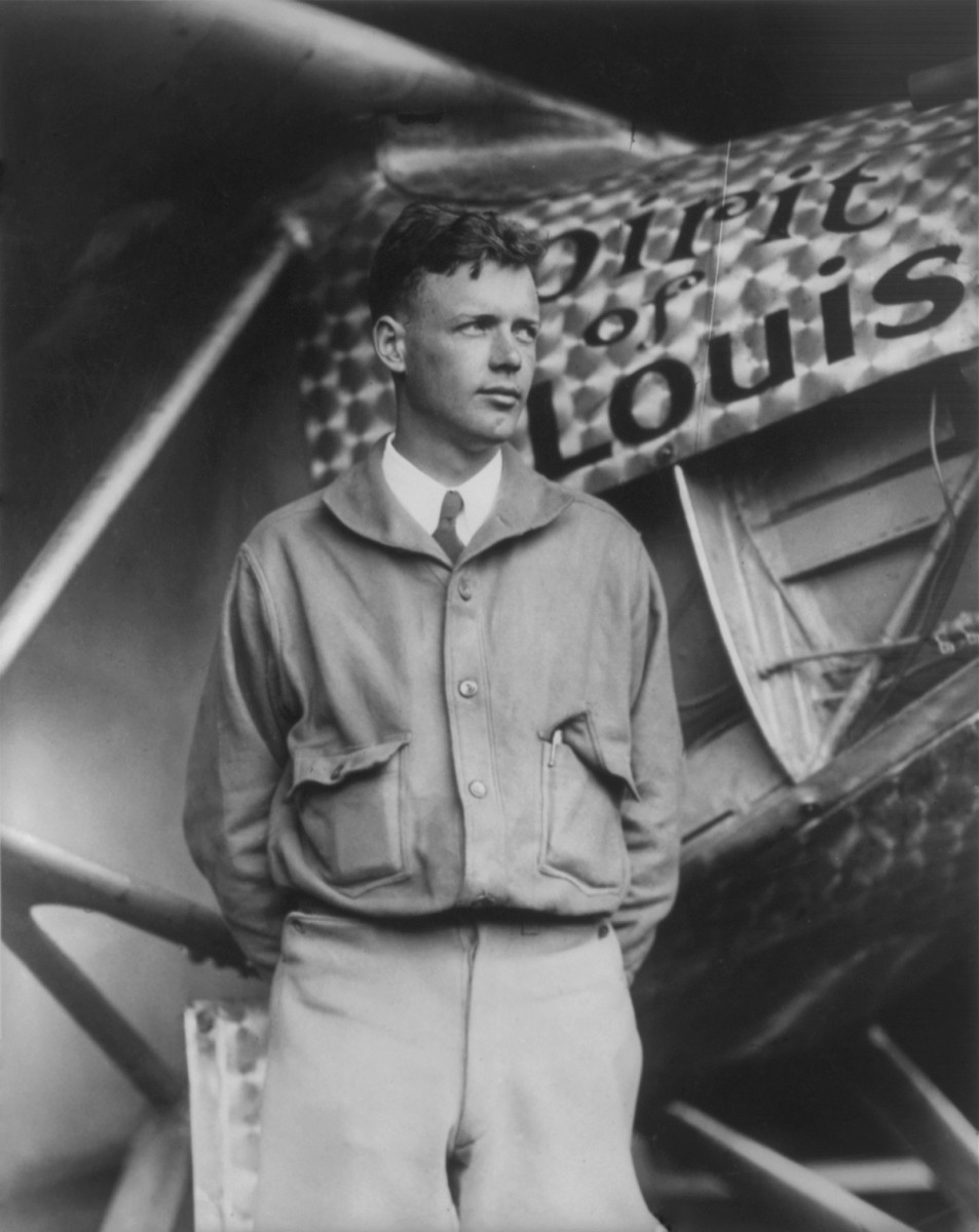 Lindbergh standing next to the Spirit of St. Louis aircraft.