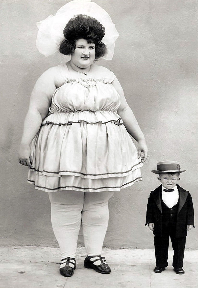 Clarence Howerton grew to be two feet four inches tall. In this image next to a lady billed as the world's biggest woman he is only nine years old.