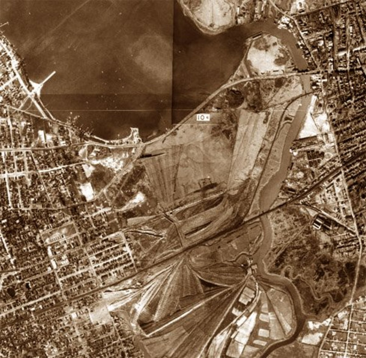 The Flushing River valley.  The river is to the right, the vast Corona Ash Dumps to the left. This early aerial photo was taken around 1915, prior to the building of Roosevelt Ave