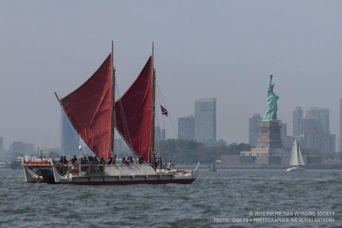 Hōkūleʻa sailing into New York Harbor past the Statue of Liberty